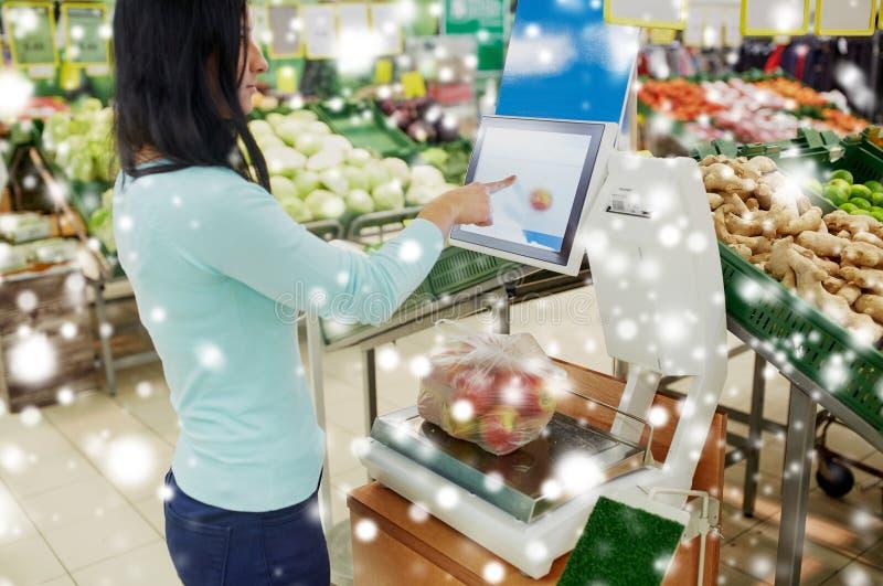 Client pesant des pommes sur l'échelle à l'épicerie photographie stock