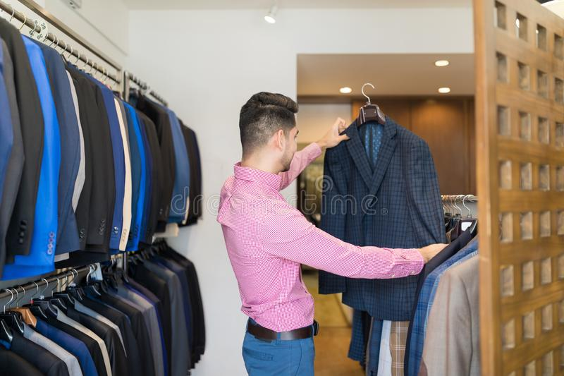 Client regardant le costume dans le magasin d'habillement photographie stock libre de droits