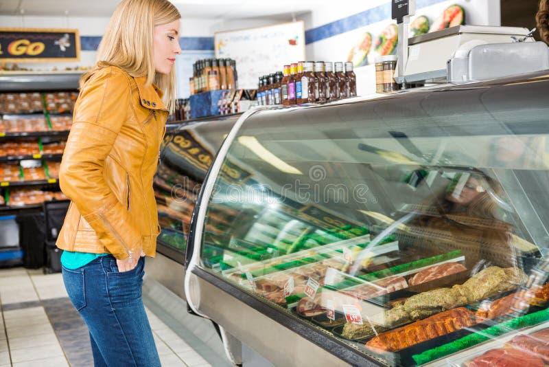 Client sélectionnant la viande à la boucherie photographie stock