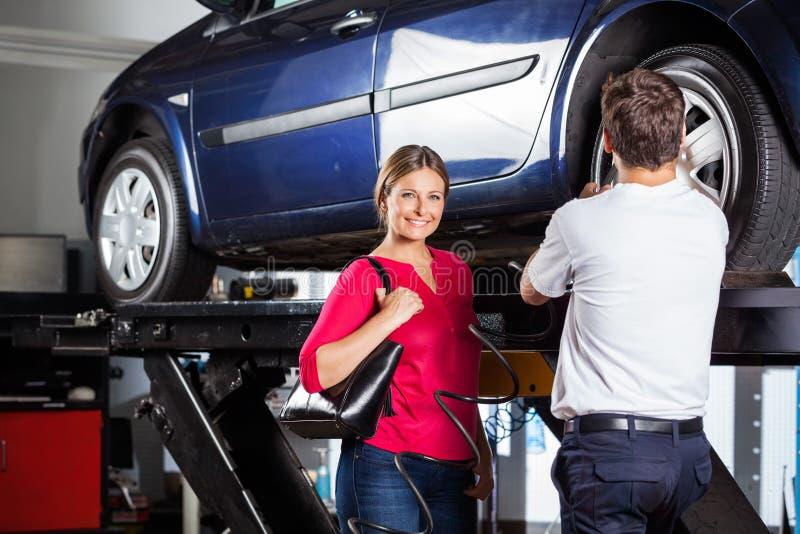 Client se tenant avec le mécanicien Refilling Tire photographie stock