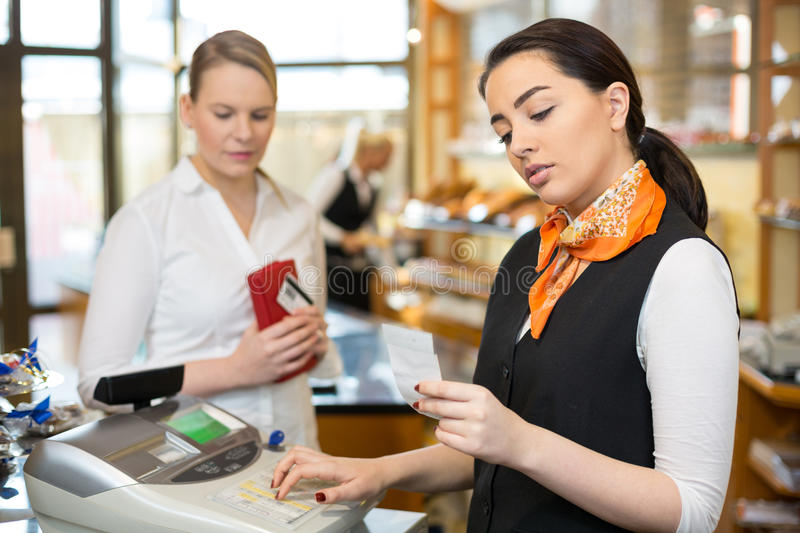 Client at shop paying at cash register. With saleswoman royalty free stock photo