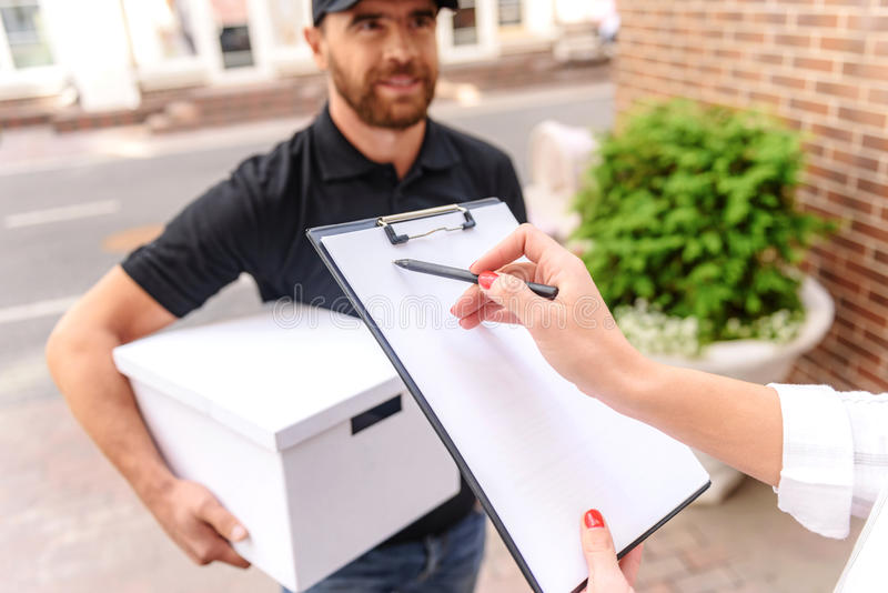 Client signant un papier dehors photo stock