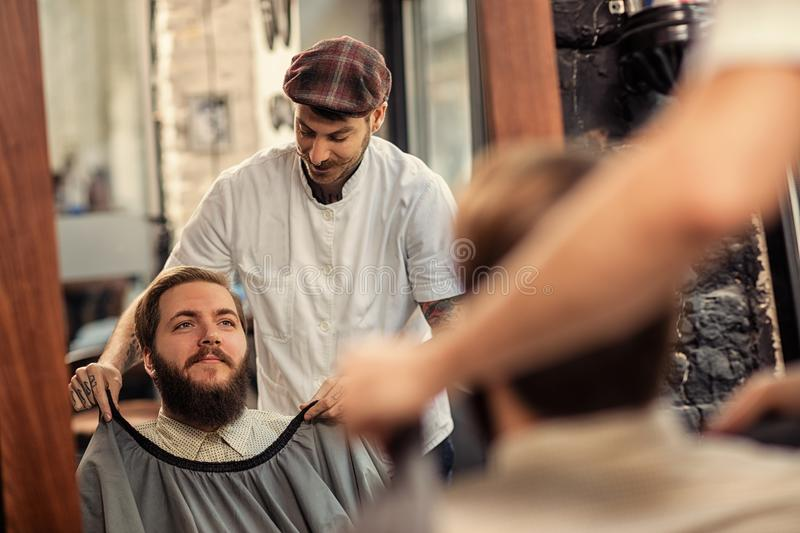 Client sitting in barber shop royalty free stock photos