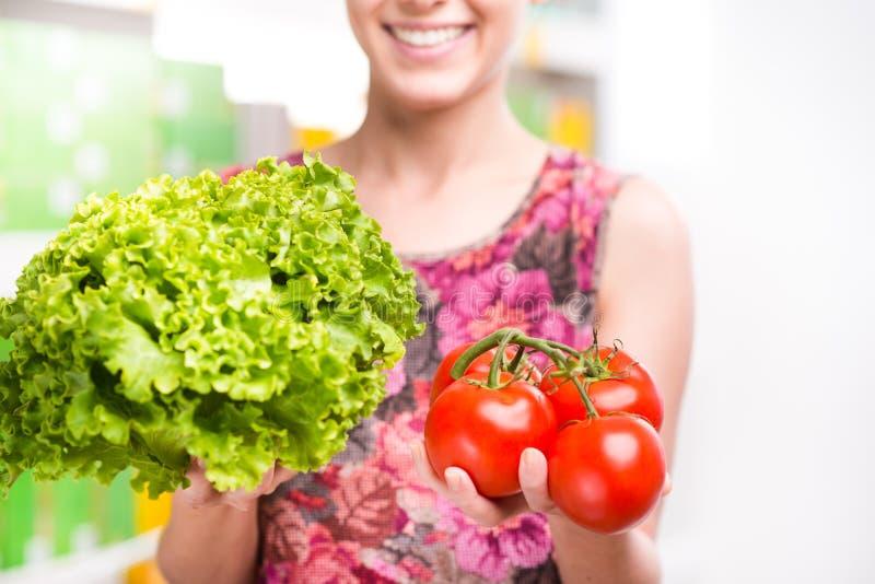 Client tenant des légumes au supermarché image stock