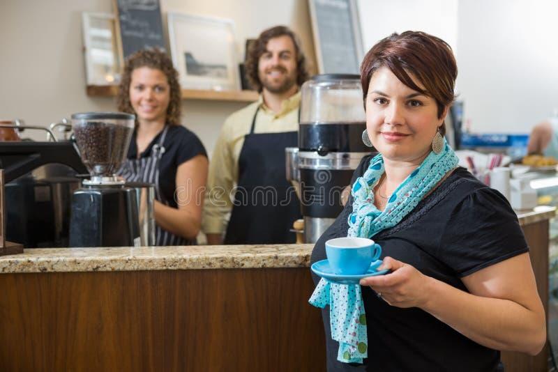 Client tenant la tasse de café avec des travailleurs au café image libre de droits