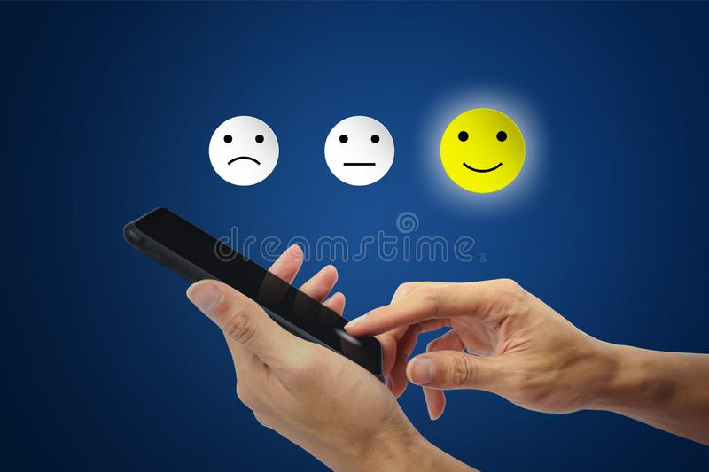 The client using hand choose happy face smile icon on smartphone royalty free stock images