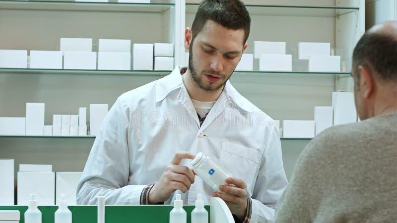 Cliente advicing dell'uomo senior delle pillole del giovane farmacista alla farmacia immagini stock libere da diritti