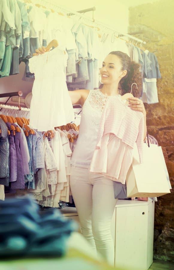 Cliente alegre de la mujer que sostiene el vestido del bebé foto de archivo