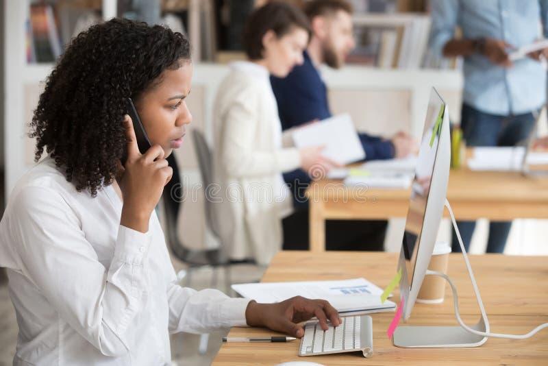 Cliente asesor afroamericano del trabajador de sexo femenino por el teléfono foto de archivo