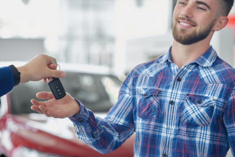Cliente atrativo na camisa azul que obtêm chave e no sorriso foto de stock royalty free