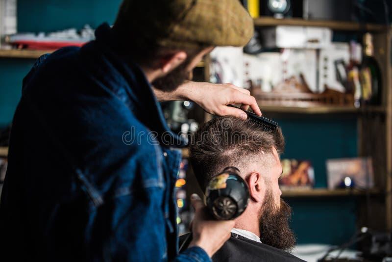 Cliente barbudo del inconformista que consigue el peinado Peluquero con la sequedad del hairdryer y pelo el diseñar del cliente P fotografía de archivo libre de regalías