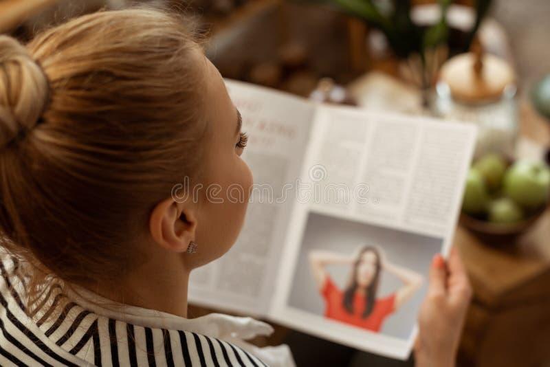 Cliente biondo messo a fuoco attentamente che legge articolo sull'argomento interessante immagini stock libere da diritti