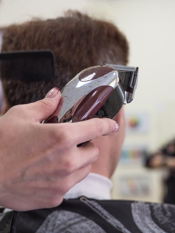 Cliente caucasiano do homem da guarni??o do barbeiro com a m?quina da tosquiadeira no barbeiro Processo masculino do tratamento d imagens de stock