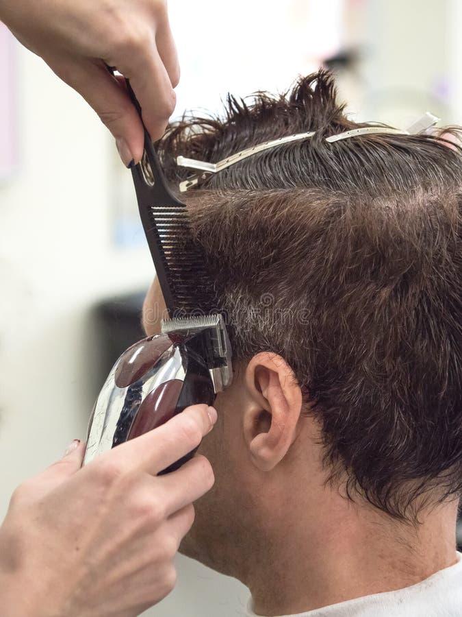 Cliente caucasiano do homem da guarni??o do barbeiro com a m?quina da tosquiadeira no barbeiro Processo masculino do tratamento d imagens de stock royalty free