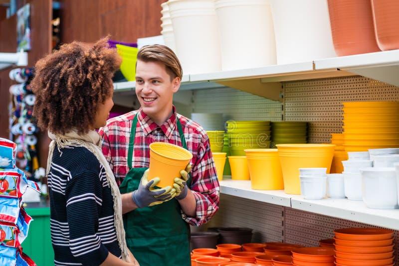 Cliente che compra i vasi di plastica al consiglio di un lavoratore utile nel negozio di fiore immagine stock libera da diritti