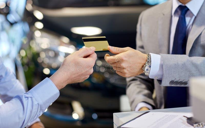 Cliente che dà credito carta al commerciante di automobile in salone fotografia stock libera da diritti