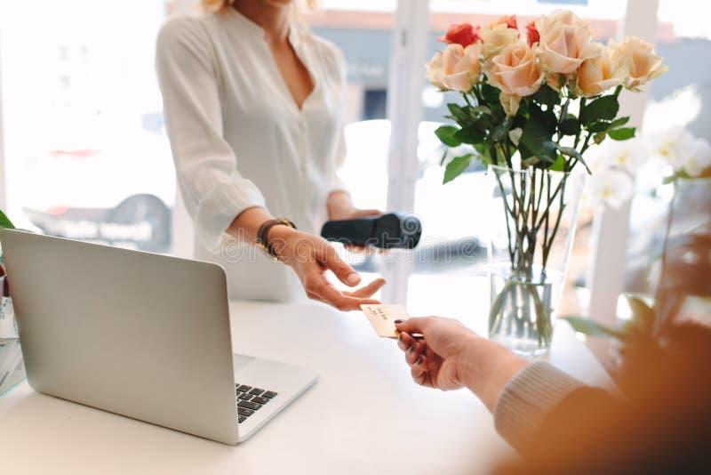 Cliente che dà credito carta al fiorista immagine stock