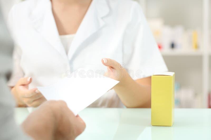 Cliente che dà ricetta ad un farmacista che richiede le medicine fotografia stock