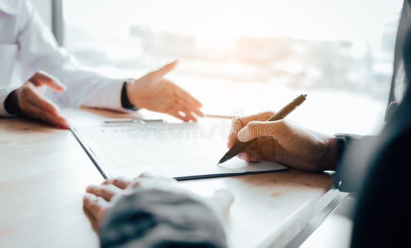 Cliente che firma un contratto del bene immobile sullo scrittorio in ufficio immagine stock