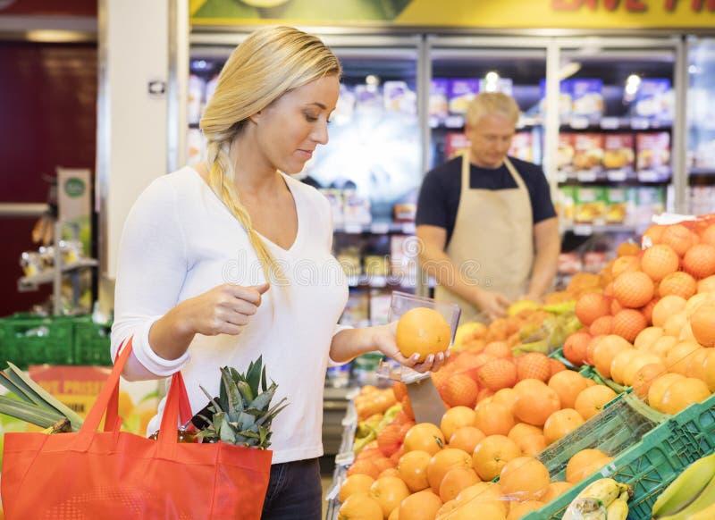 Cliente che giudica arancio in drogheria immagine stock