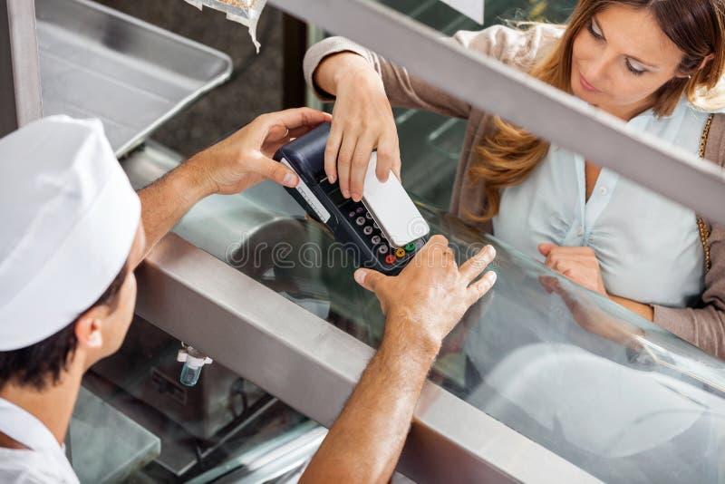 Cliente che paga con Smartphone alla macelleria fotografia stock