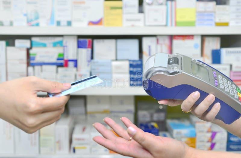 Cliente che paga con una carta di credito nella farmacia della farmacia fotografia stock libera da diritti