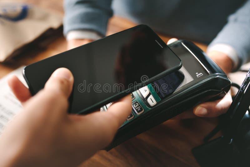 Cliente che paga tramite lo smartphone facendo uso della tecnologia di NFC fotografia stock libera da diritti
