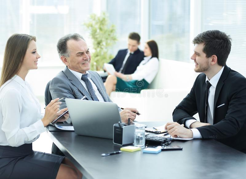 Cliente che parla con il personale allo scrittorio nell'ufficio fotografia stock