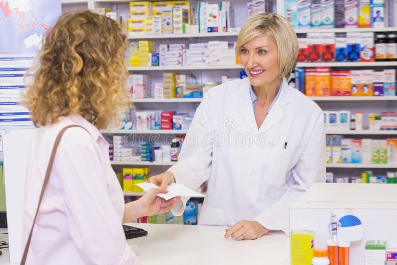 Cliente che passa una prescrizione ad un farmacista sorridente immagine stock libera da diritti