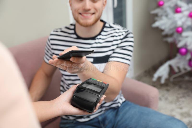 Cliente che per mezzo dello smartphone e del terminale POS di credito per non il pagamento in contanti immagine stock libera da diritti