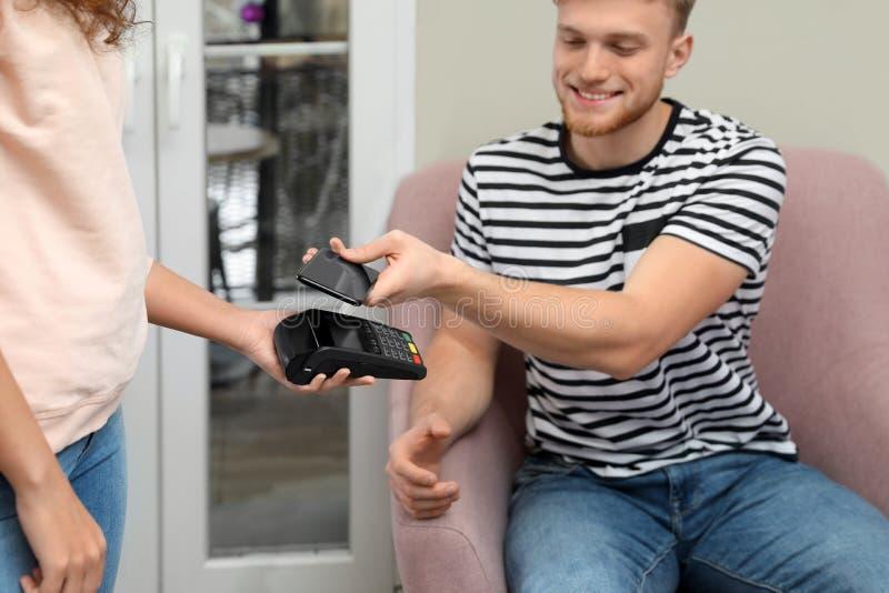 Cliente che per mezzo dello smartphone e del terminale POS di credito per non il pagamento in contanti fotografia stock