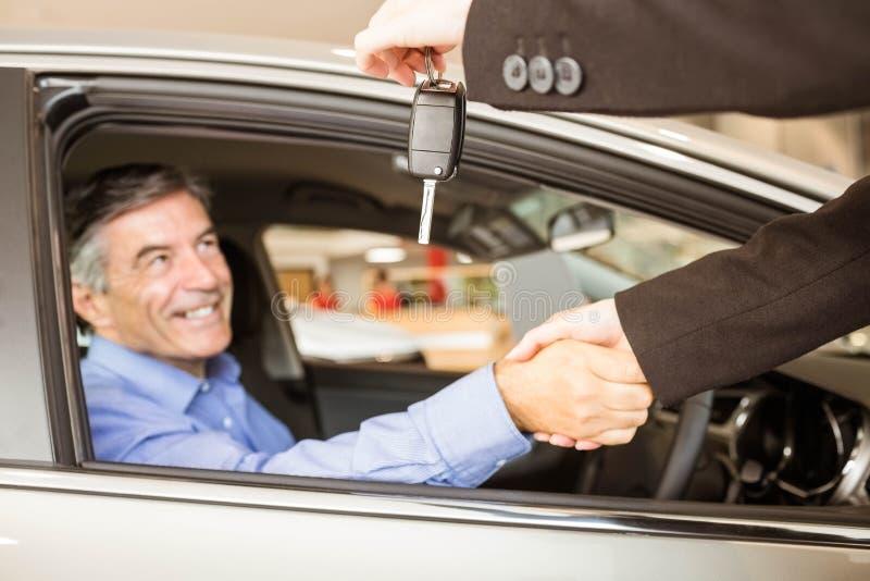 Cliente che riceve le chiavi dell'automobile mentre stringendo mano immagini stock libere da diritti