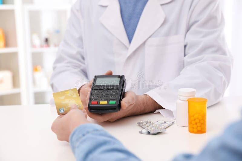 Cliente che utilizza la carta di credito per il pagamento terminale nella farmacia fotografia stock libera da diritti