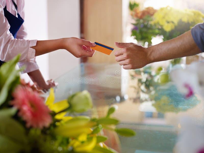 Cliente com compra de cartão do crédito na loja de flores fotografia de stock