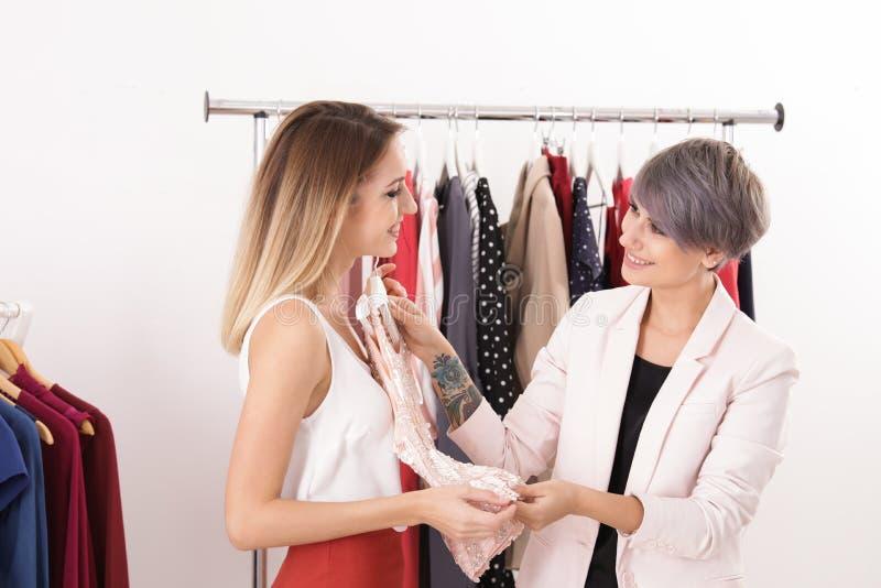 Cliente d'aiuto del giovane stilista per scegliere i vestiti d'avanguardia fotografia stock