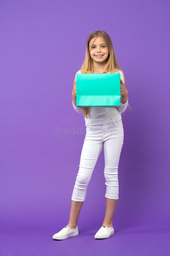 Cliente da criança no vestuário desportivo no fundo violeta Criança pequena com saco de compras Sorriso feliz da menina com o sac fotos de stock royalty free