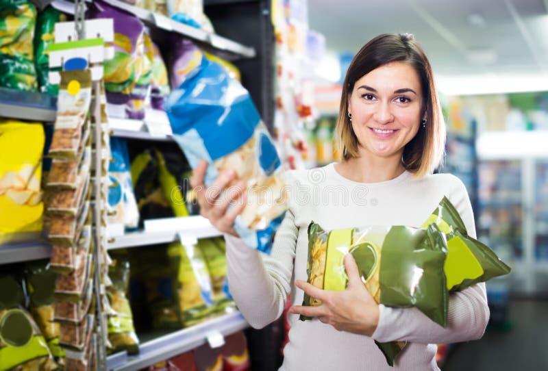 Cliente da moça que procura petiscos saborosos no supermercado imagem de stock royalty free