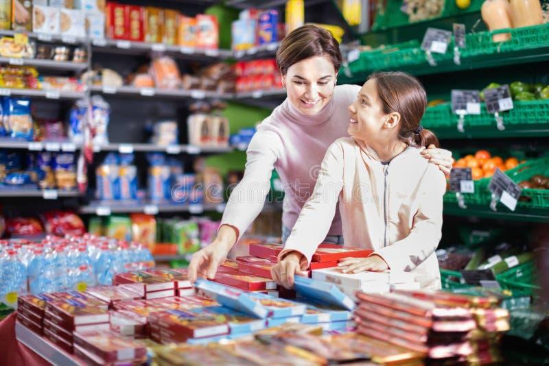 Cliente da mulher com a menina que procura cookies saborosos imagens de stock royalty free