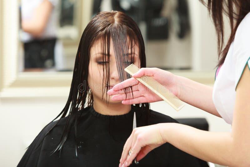 Cliente da mulher do cabelo do corte do barbeiro no salão de beleza do cabeleireiro fotografia de stock