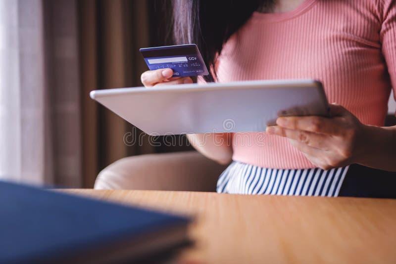 Cliente da mulher que usa o cartão e a tabuleta de crédito à compra em linha foto de stock royalty free