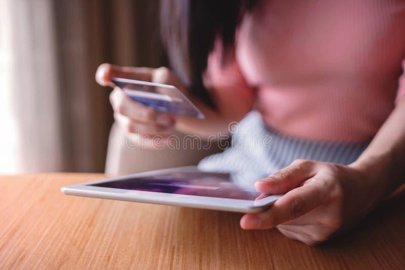 Cliente da mulher que usa o cartão e a tabuleta de crédito à compra em linha fotografia de stock royalty free
