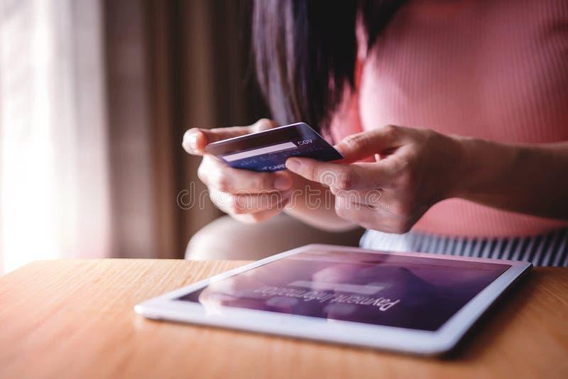 Cliente da mulher que usa o cartão e a tabuleta de crédito à compra em linha Tiro do close-up foto de stock royalty free