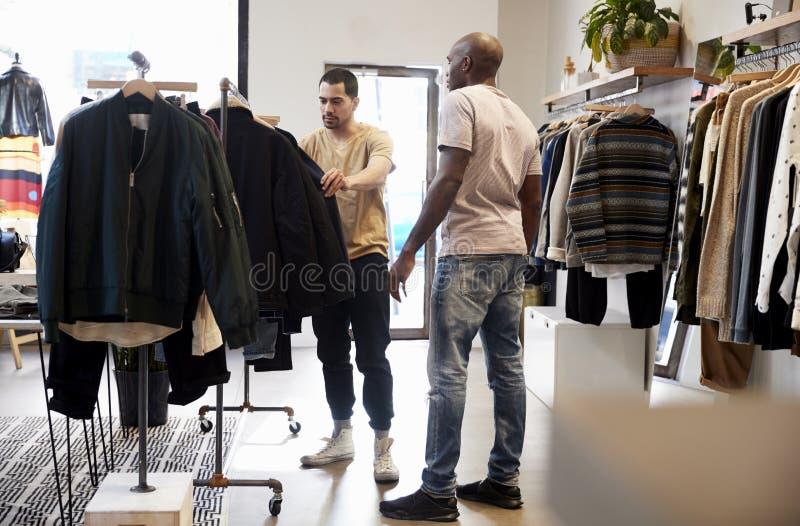 Cliente de ajuda do assistente de loja em uma loja de roupa do ½ s do ¿ do menï foto de stock royalty free