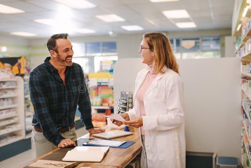 Cliente de ayuda del farmacéutico en la farmacia imagen de archivo