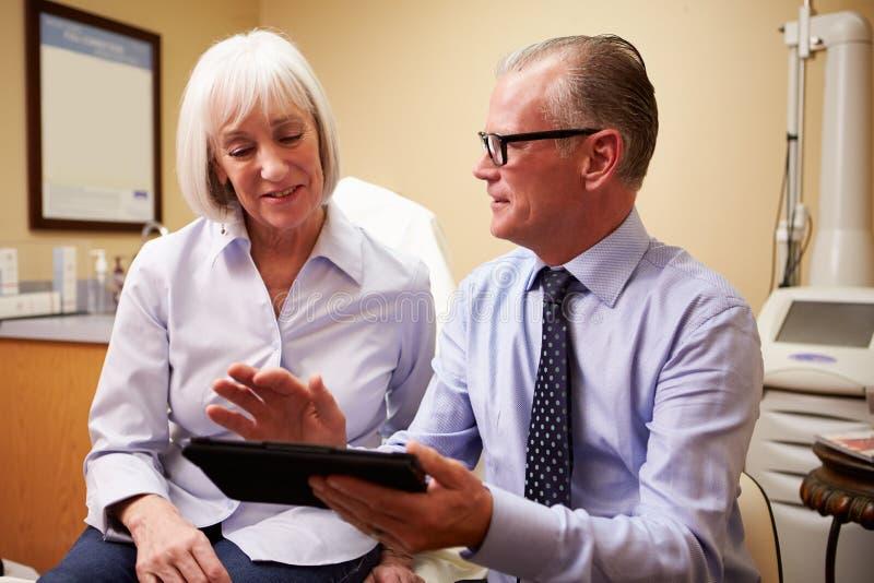 Cliente de Discussing Procedure With do cirurgião cosmético no escritório imagens de stock royalty free