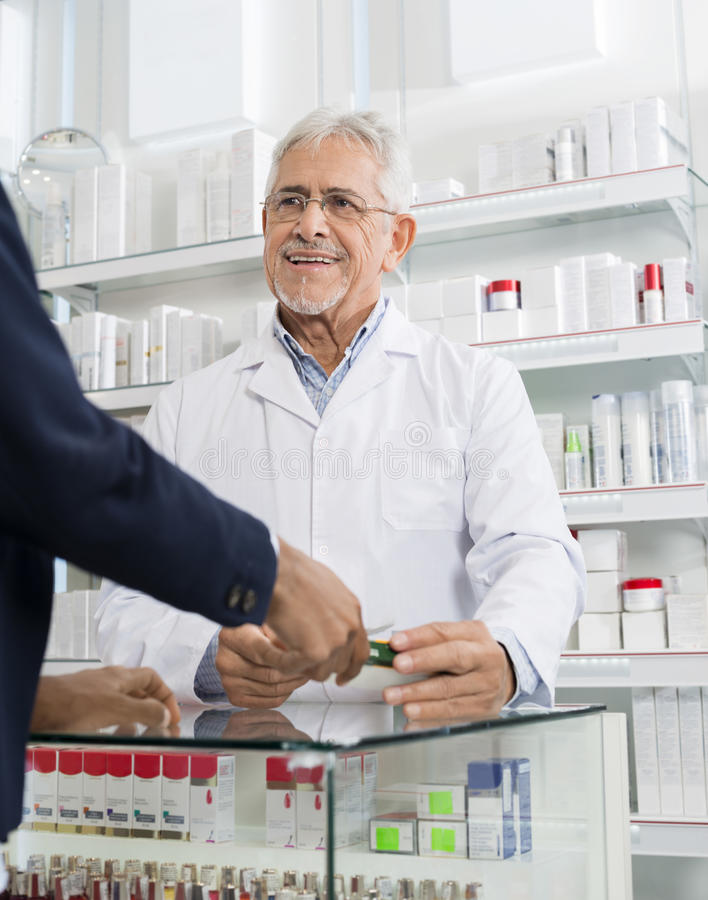 Cliente de Giving Medicine To del químico en farmacia imagen de archivo