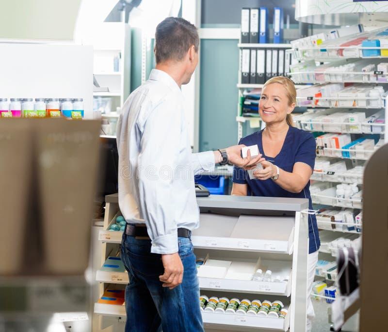 Cliente de Giving Product To del farmacéutico en farmacia imágenes de archivo libres de regalías