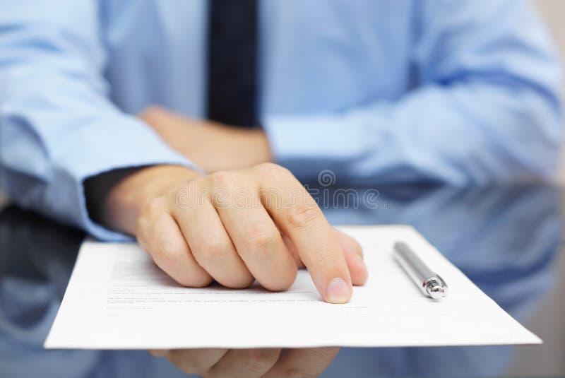 Cliente de la demostración del hombre de negocios donde firmar foto de archivo libre de regalías