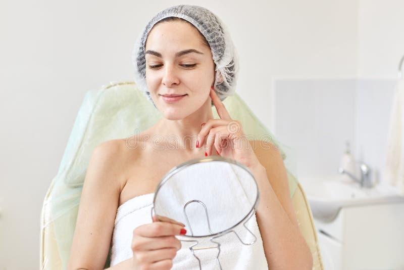 Cliente de la mujer del salón de la cosmetología satisfecho con resultado del procedimiento cosmético En espejo de mirada femenin imágenes de archivo libres de regalías