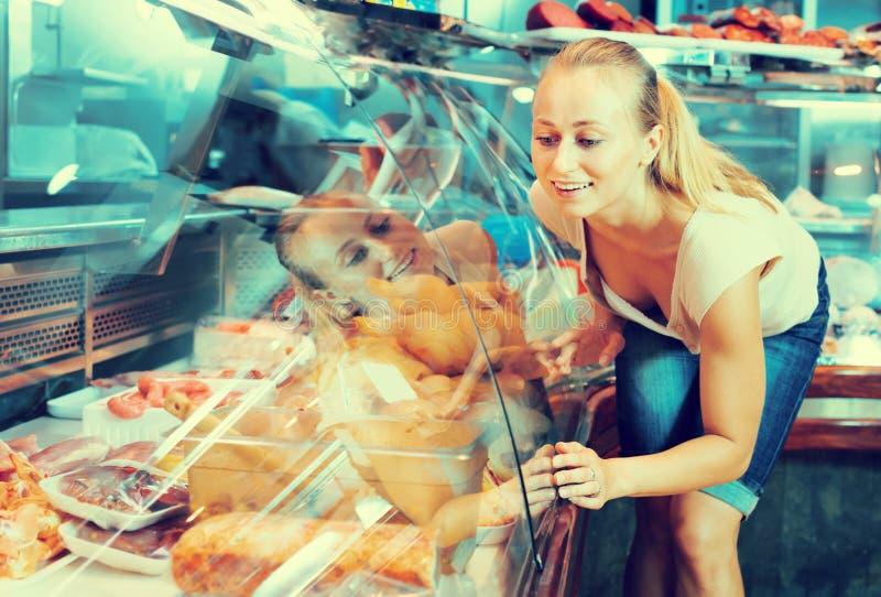 Cliente de la mujer joven que mira piezas del pollo imagen de archivo libre de regalías